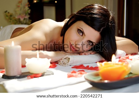beautiful woman relaxing at spa salon lying on a spa  table with candles - stock photo