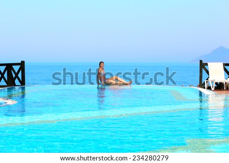 Beautiful woman relaxing at the edge of infinity pool at luxury resort - stock photo
