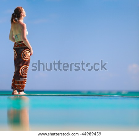 Beautiful woman relaxing by infinity swimming pool - stock photo