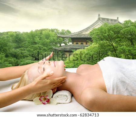 Beautiful woman relaxing during a massage with oriental pagoda on the background - stock photo
