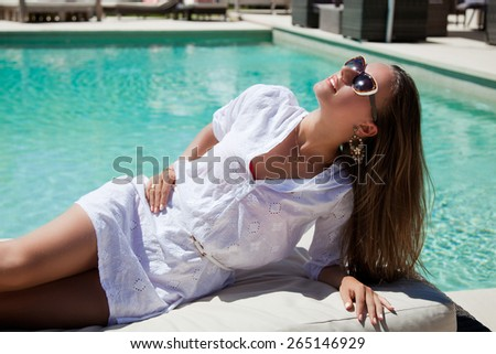 Beautiful woman relaxing enjoying sun at the luxury poolside, tanning. Girl at travel spa resort pool. Summer luxury vacation.  - stock photo