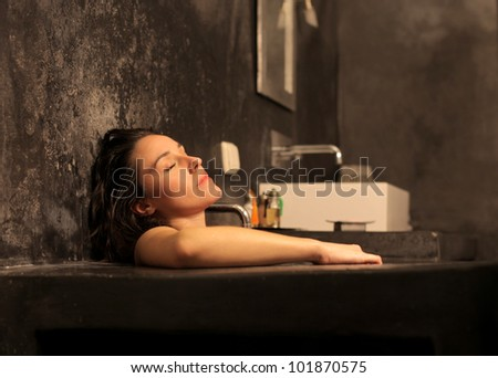 Beautiful woman relaxing in a bathtub - stock photo