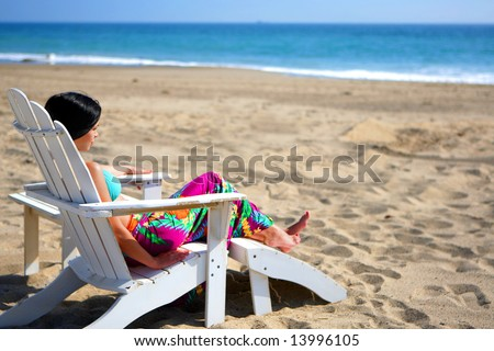 Beautiful woman relaxing in a chair on the beach - stock photo