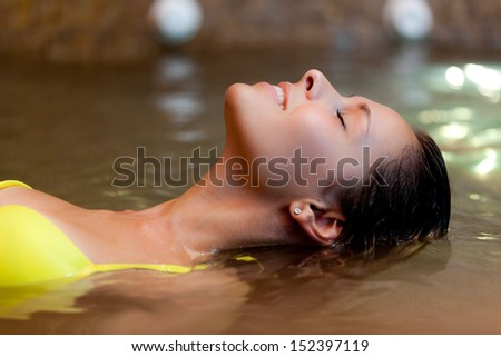 Beautiful woman relaxing in a jacuzzi - stock photo
