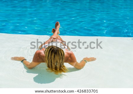 Beautiful woman relaxing in a pool at summer resort - stock photo