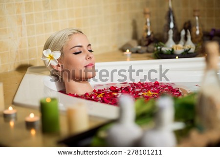 Beautiful woman relaxing in bath with petals - stock photo