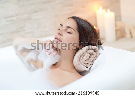 Beautiful woman relaxing in bathtub - stock photo