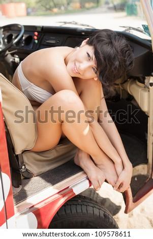 Beautiful woman relaxing in car near the beach - outdoors - stock photo