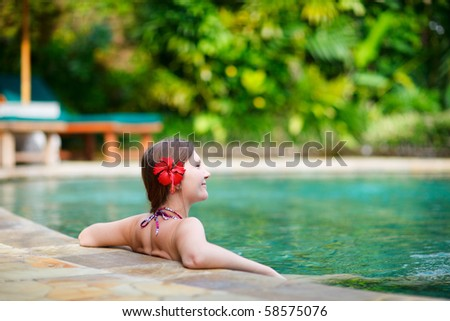 Beautiful woman relaxing in infinity swimming pool - stock photo