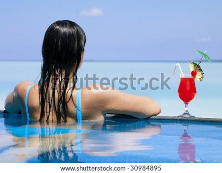 Beautiful woman relaxing in swimming pool - stock photo