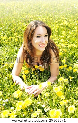 beautiful woman relaxing in the grass and flowers - stock photo