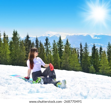 Beautiful woman relaxing in the mountains sitting on a snowboard in the winter. Carpathian Mountains. Bukovel. - stock photo