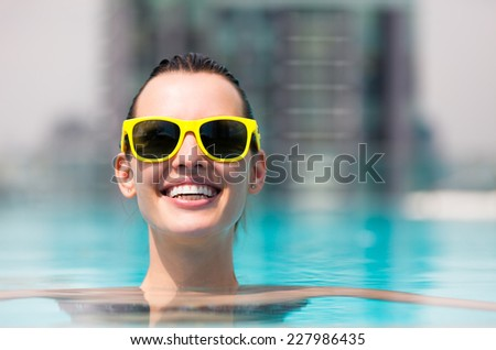 Beautiful woman relaxing in the pool - stock photo