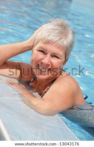 beautiful woman relaxing in the swimming pool - stock photo