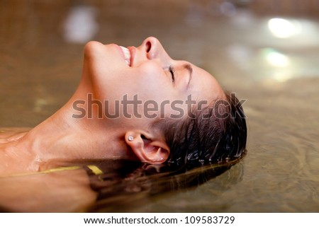 Beautiful woman relaxing in the water in a spa - stock photo
