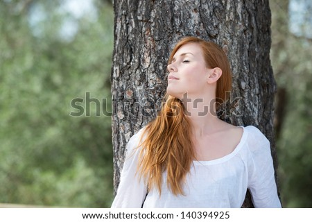 Beautiful woman relaxing in woodland standing leaning against the trunk if a tree with her eyes closed in enjoyment and bliss - stock photo