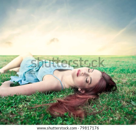 Beautiful woman relaxing on a green meadow - stock photo
