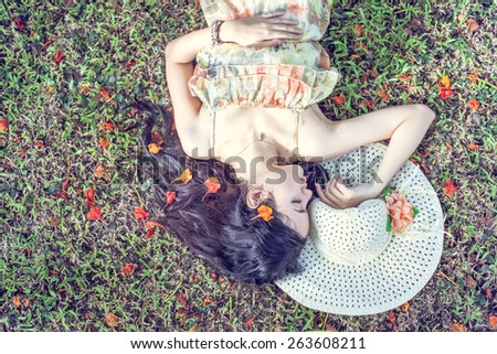 Beautiful woman relaxing on a green meadow with flower, vintage color tone - stock photo