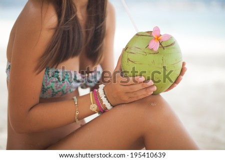 Beautiful woman relaxing on a paradise beach with coconut