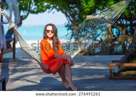 Beautiful woman relaxing on hammock during summer vacation - stock photo