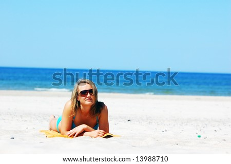 Beautiful woman relaxing on the beach. Lots of useful copyspace