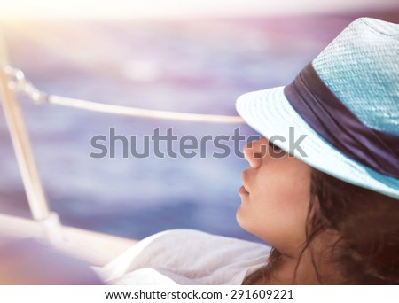 Beautiful woman relaxing on the deck of sailboat in sunny day and tanning, enjoying peaceful luxury summer vacation on a sea cruise