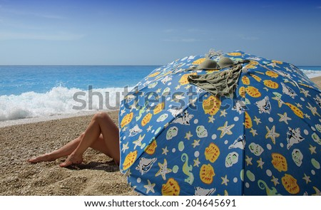 beautiful woman relaxing under colorful umbrella  - stock photo
