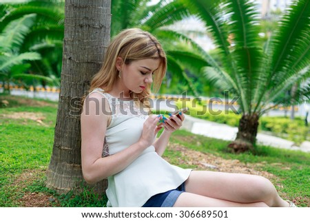Beautiful Woman Resting At The Park And Talking On Mobile Phone - stock photo
