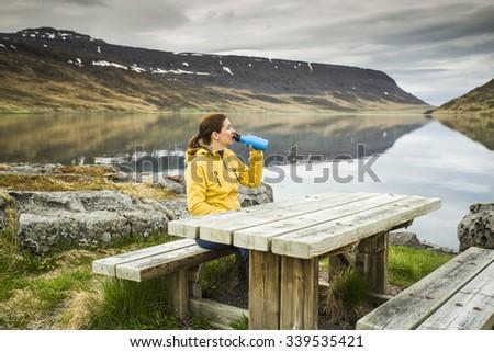Beautiful woman resting close to a beautiful lake - stock photo