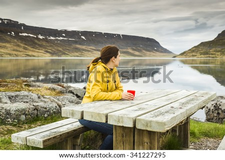 Beautiful woman resting close to a beautiful lake and drinkign a tea - stock photo