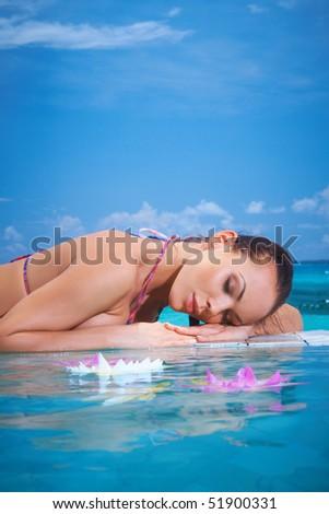Beautiful woman resting near pool at Maldives - stock photo