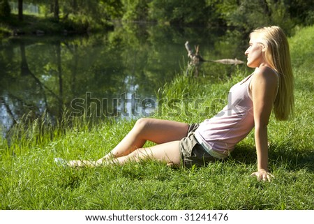 Beautiful woman resting on river, green environment