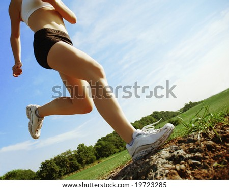 Beautiful woman runner in front of blue sky, low angle. - stock photo