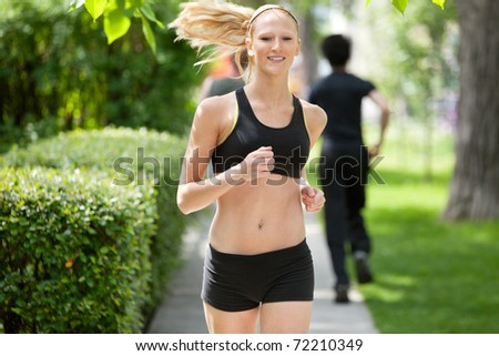 Beautiful woman running in park with people in the background - stock photo