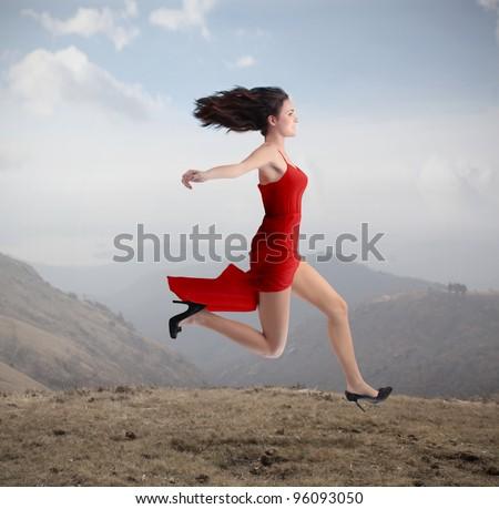 Beautiful woman running on a hill - stock photo