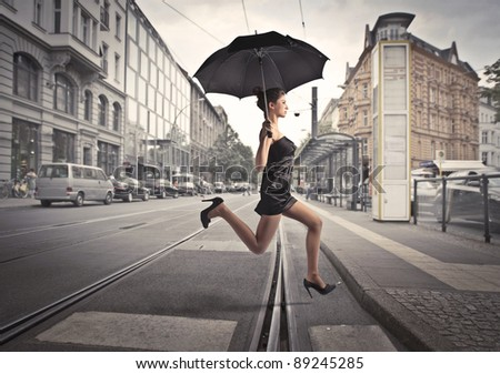 Beautiful woman running under an umbrella on a city street