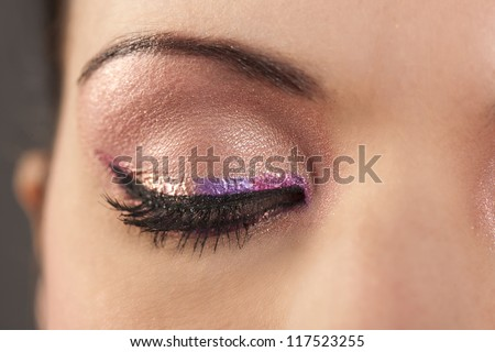 Beautiful woman's closed eye with rainbow pink eyeliner