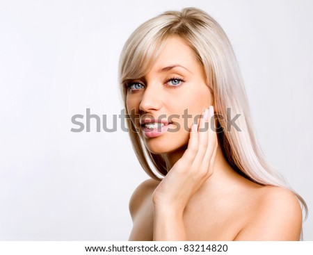 Beautiful woman's face with fresh clean skin - isolated on gray background