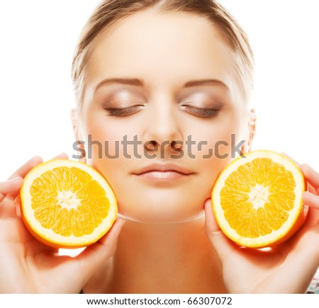 Beautiful woman's face with juicy orange - stock photo