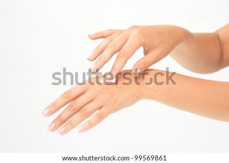 Beautiful woman's hands applying cream - stock photo