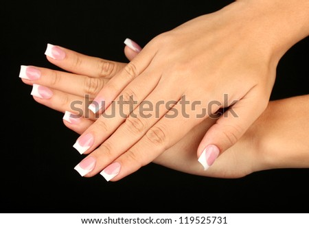 Beautiful woman's hands with french manicure on black background