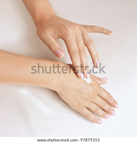 Beautiful woman's hands with pink care cream on the palm - stock photo