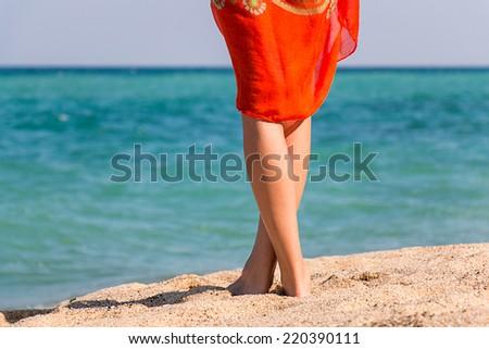 Beautiful woman's legs on sandy beach. - stock photo