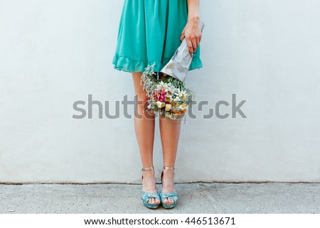Beautiful woman's legs. Woman holding a bouquet of flowers - stock photo
