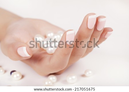 Beautiful woman's nails with french manicure and pearls. - stock photo