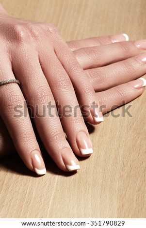 Beautiful woman's nails with perfect french manicure on natural wood background. Care for female hands. Natural look with light nail polish, beauty care.  - stock photo