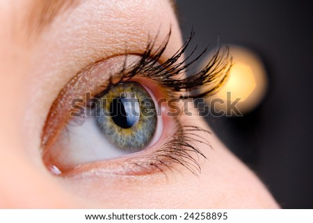 beautiful woman's open  eye over dark background