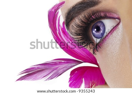 Beautiful woman`s open eye. Pink feathers on background. - stock photo