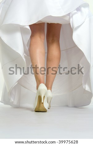 Beautiful woman's torso with long legs in white wedding dress - stock photo