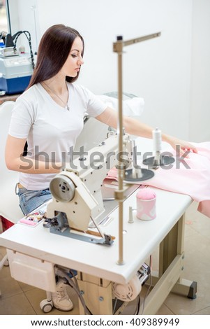 beautiful woman seamstress sew on the sewing machine clothes. sewing workshop